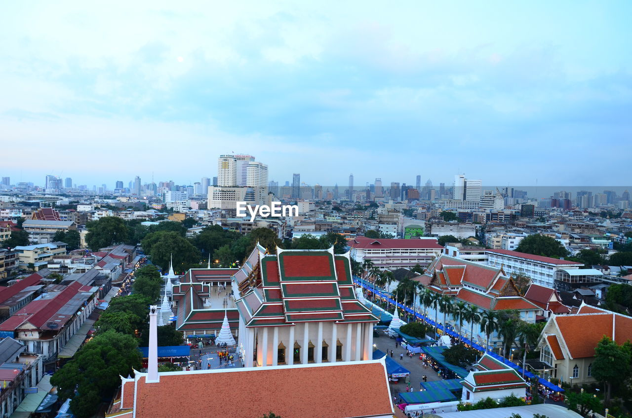 architecture, building exterior, built structure, sky, crowded, cloud - sky, residential building, cityscape, outdoors, city, day, roof, tree