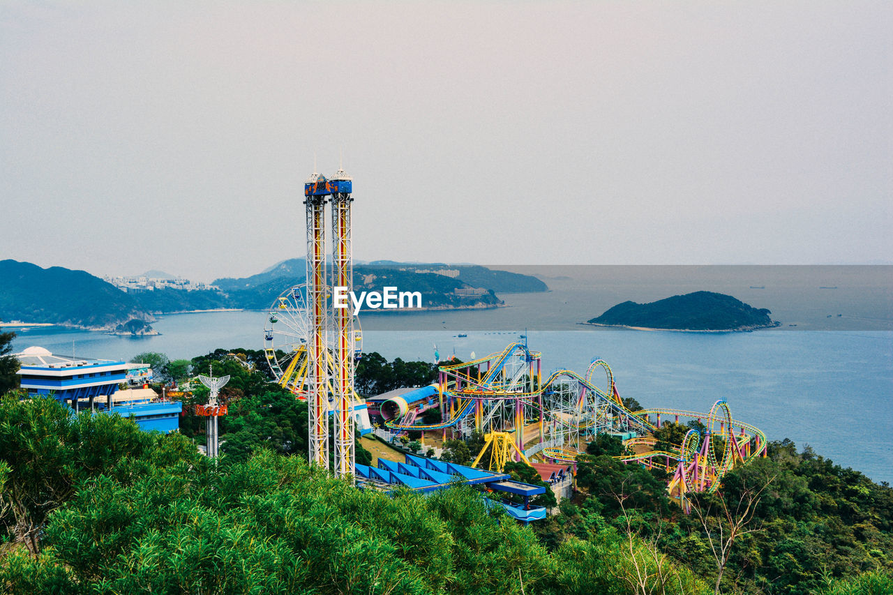 High angle view of rides at amusement park with sea in background