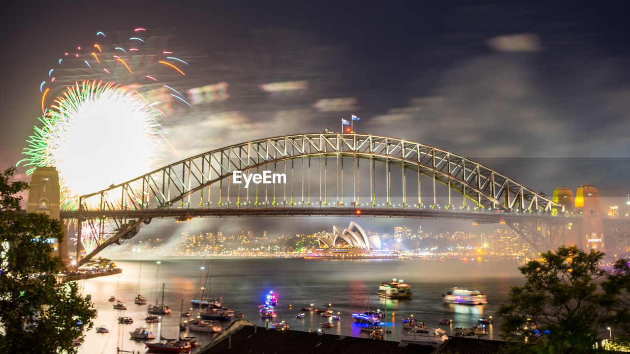 Sydney Harbor Bridge Over Parramatta River With Firework Display Against Sky At Night