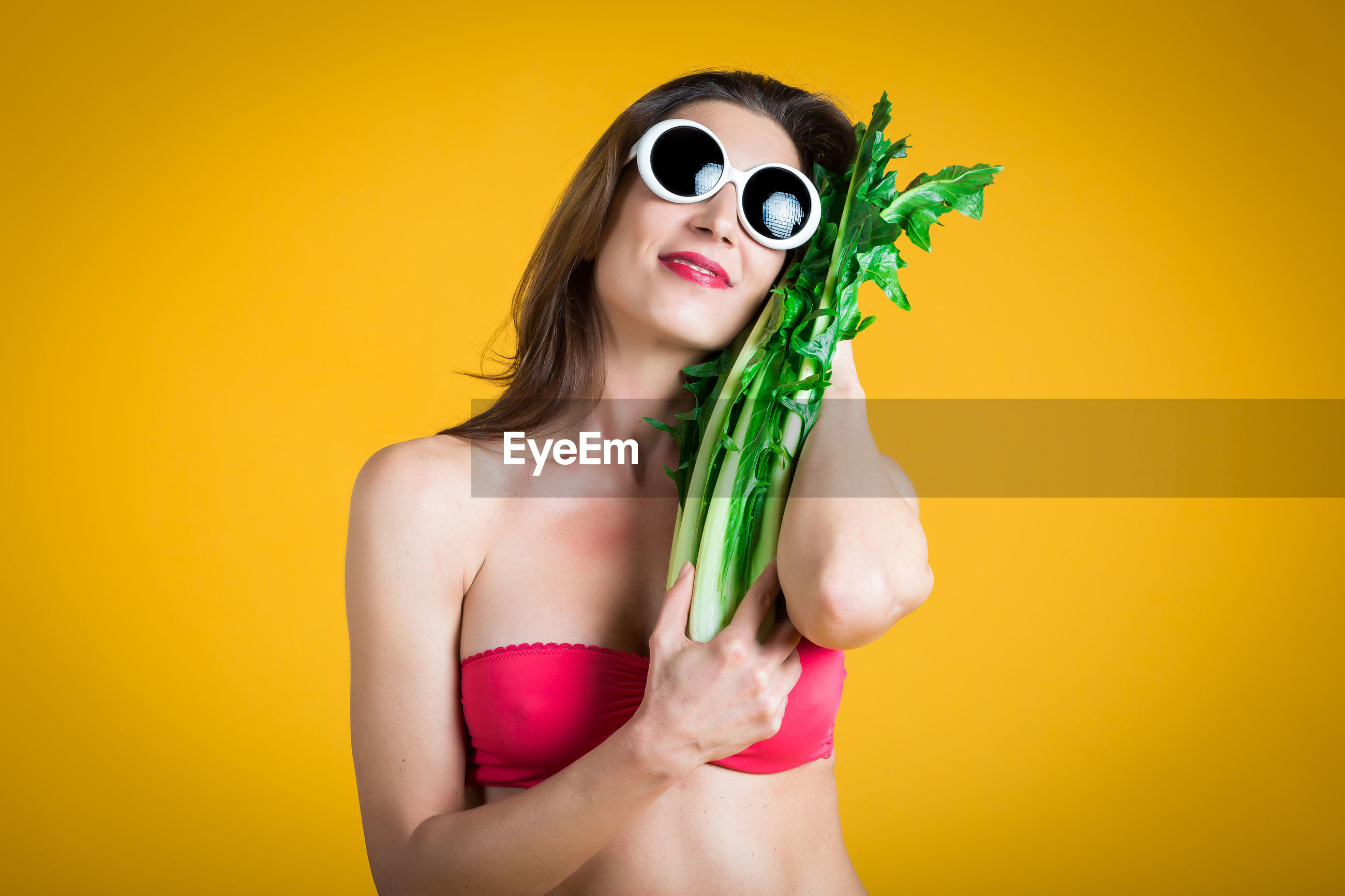 Woman holding vegetable against yellow background