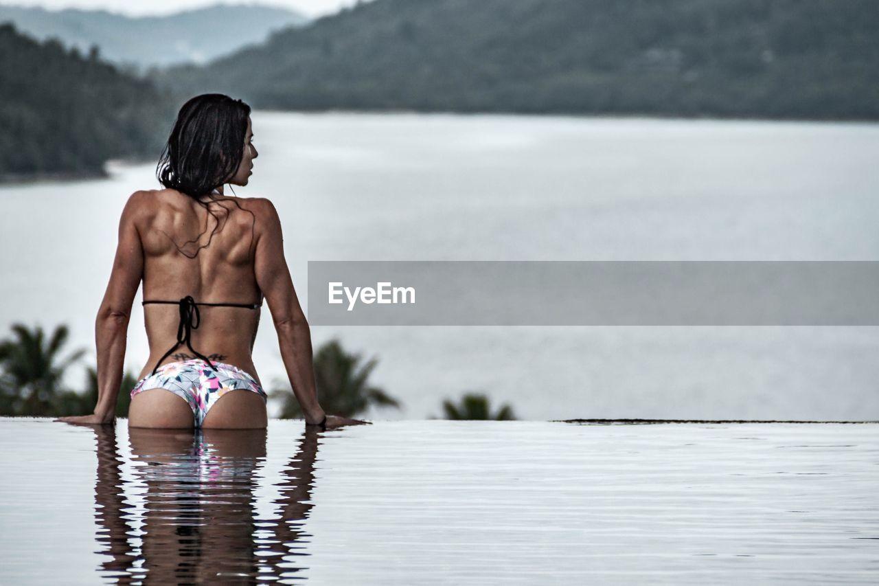Rear View Of Mid Adult Woman Wearing Bikini Swimming In Infinity Pool
