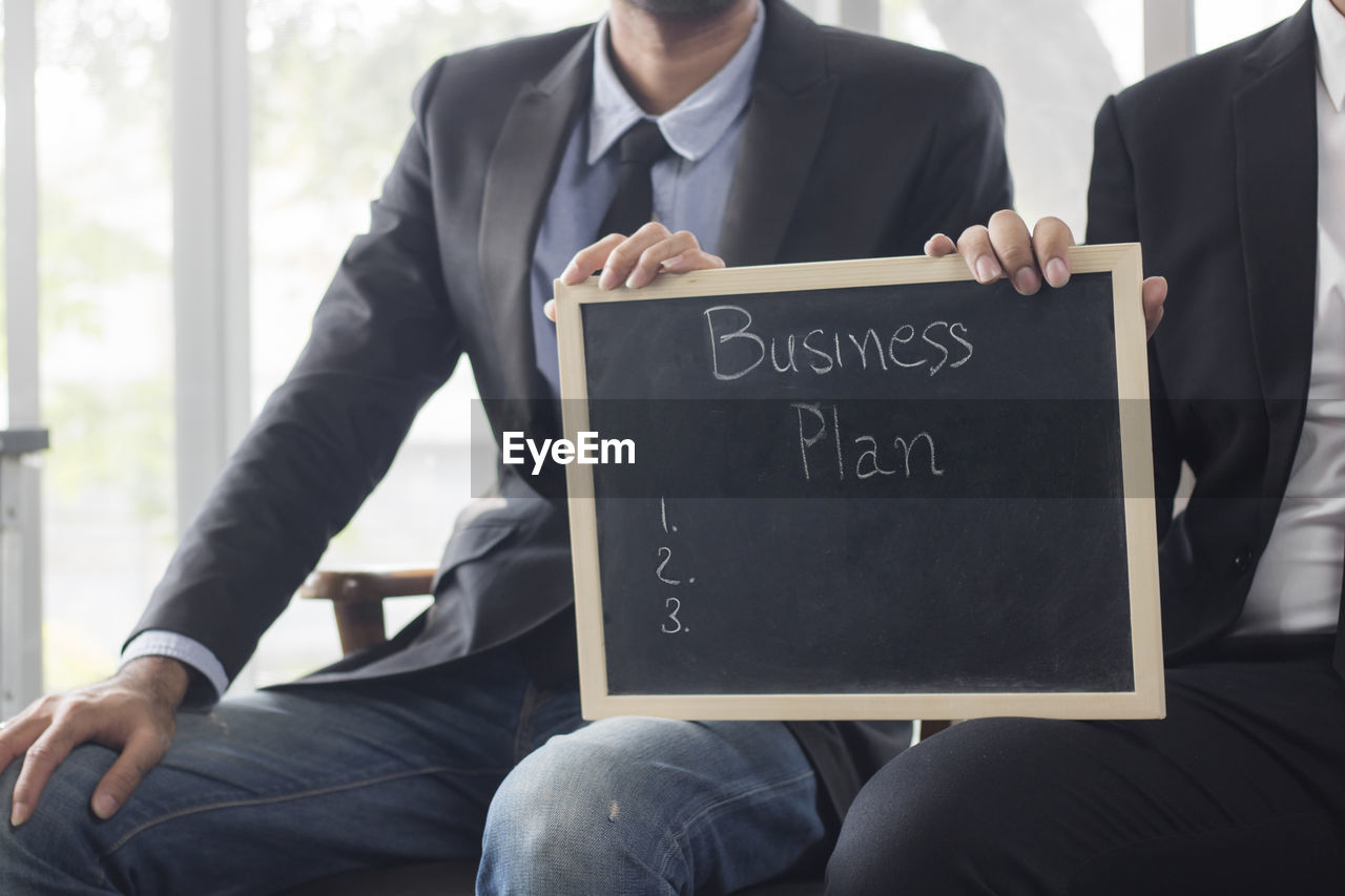 Midsection of business people holding slate while sitting on chair