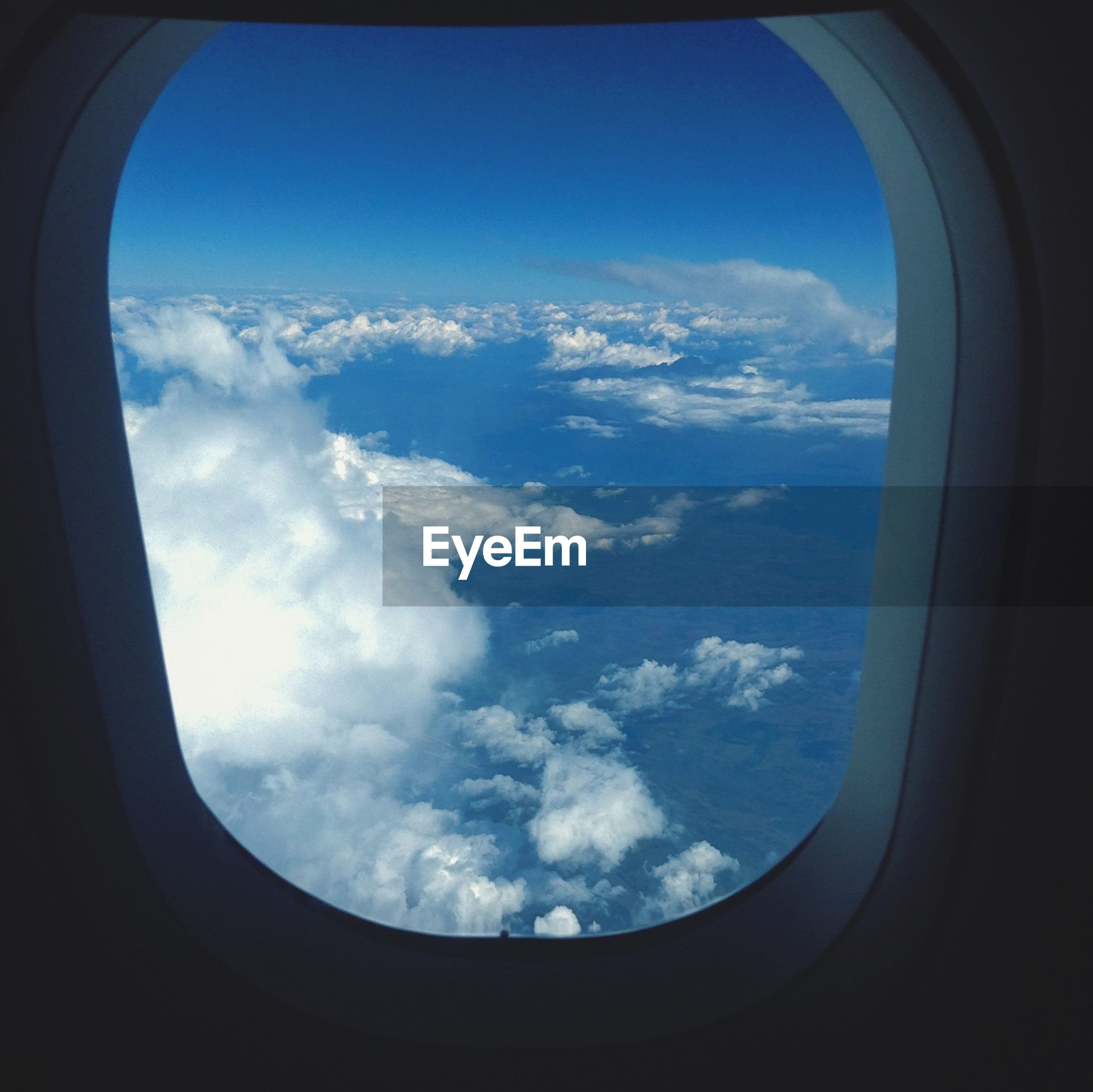window, airplane, vehicle interior, sky, transportation, air vehicle, transparent, glass - material, mode of transport, indoors, cloud - sky, cloud, looking through window, flying, part of, cloudscape, scenics, journey, blue, travel