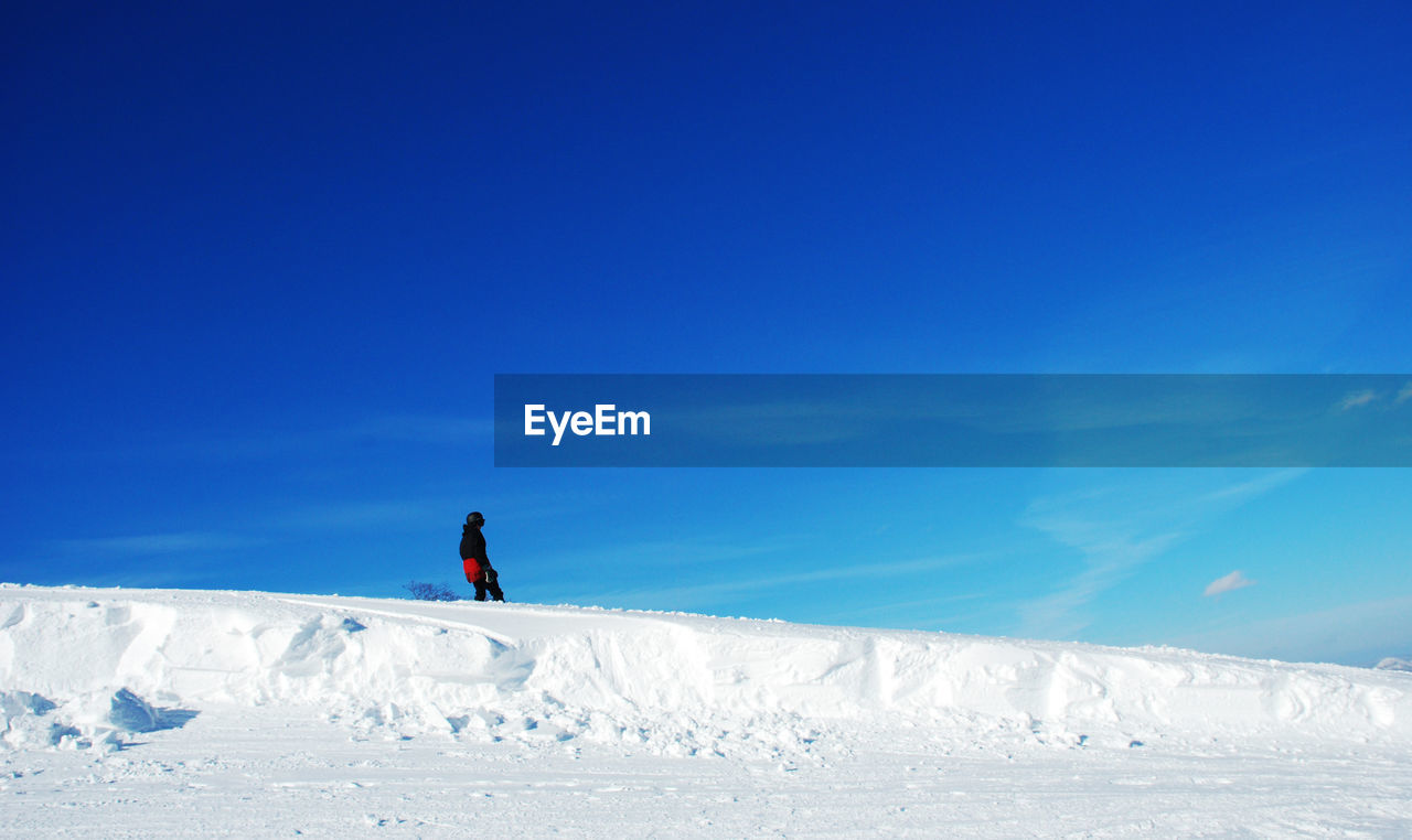 One Person Walking On Snowy Area Against Clear Sky