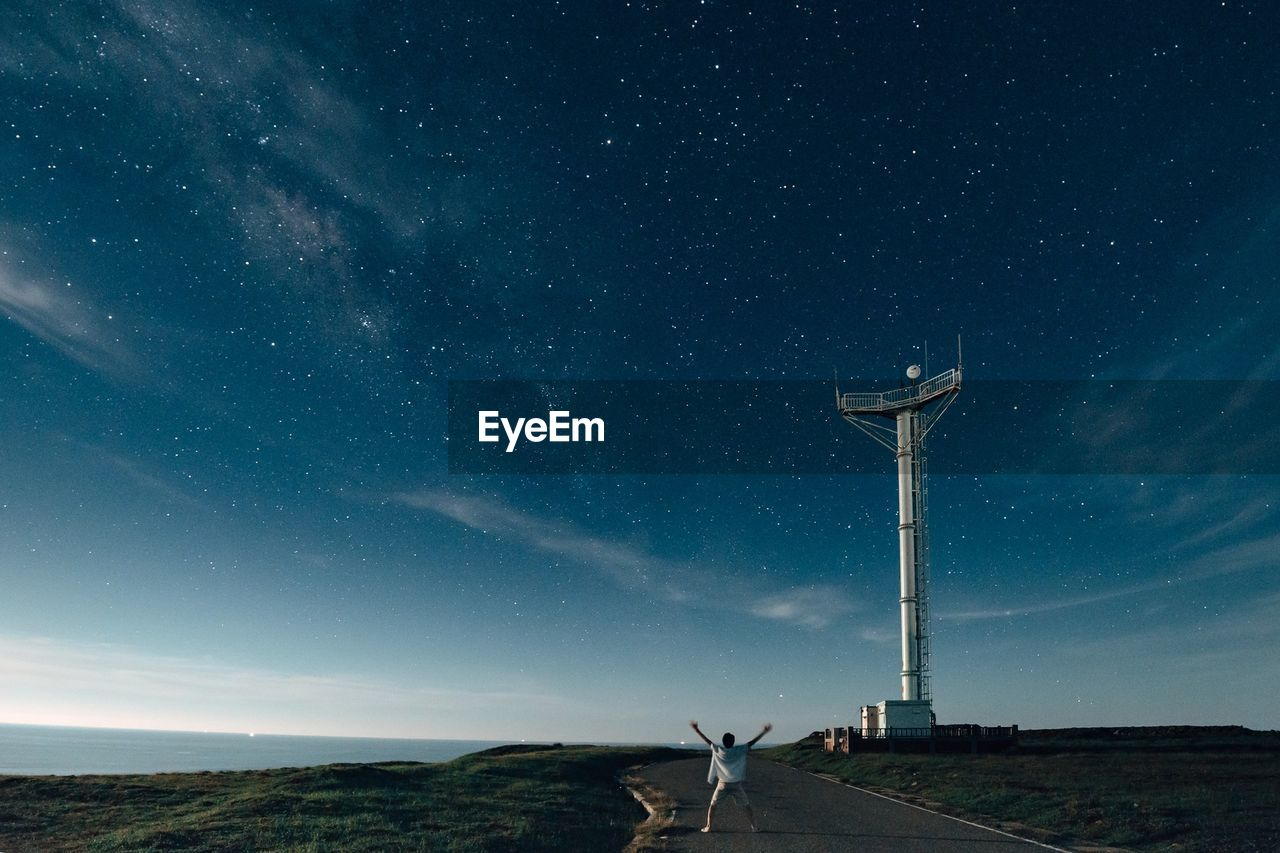 Rear View Of Man Standing By Communication Tower Against Star Field At Dusk