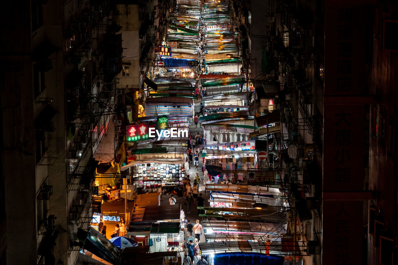 High angle view of illuminated market amidst buildings in city during night
