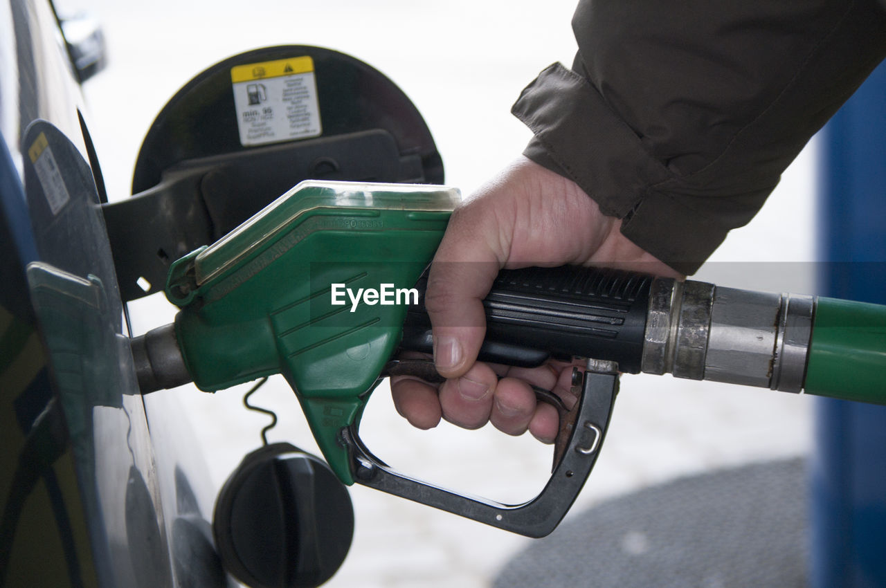 Cropped Hand Of Man Refueling Car At Gas Station