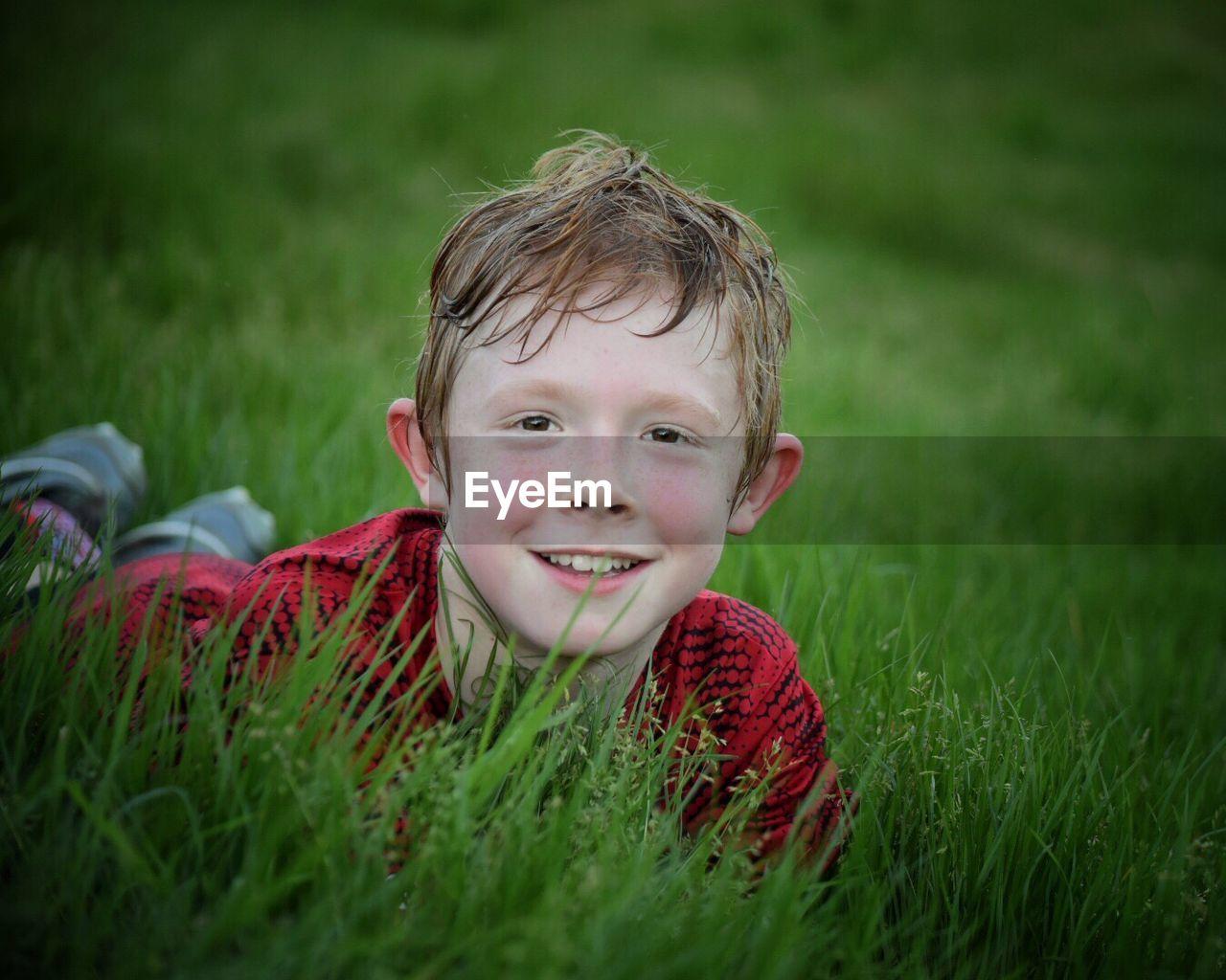 Portrait Of Smiling Boy Lying Down On Grassy Field
