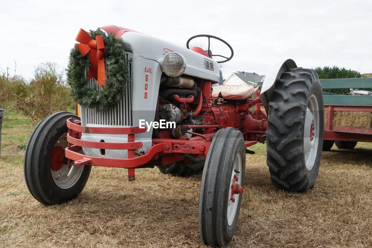 transportation, field, land vehicle, day, agricultural machinery, mode of transport, outdoors, agriculture, tree, no people, rural scene, combine harvester, sky, nature