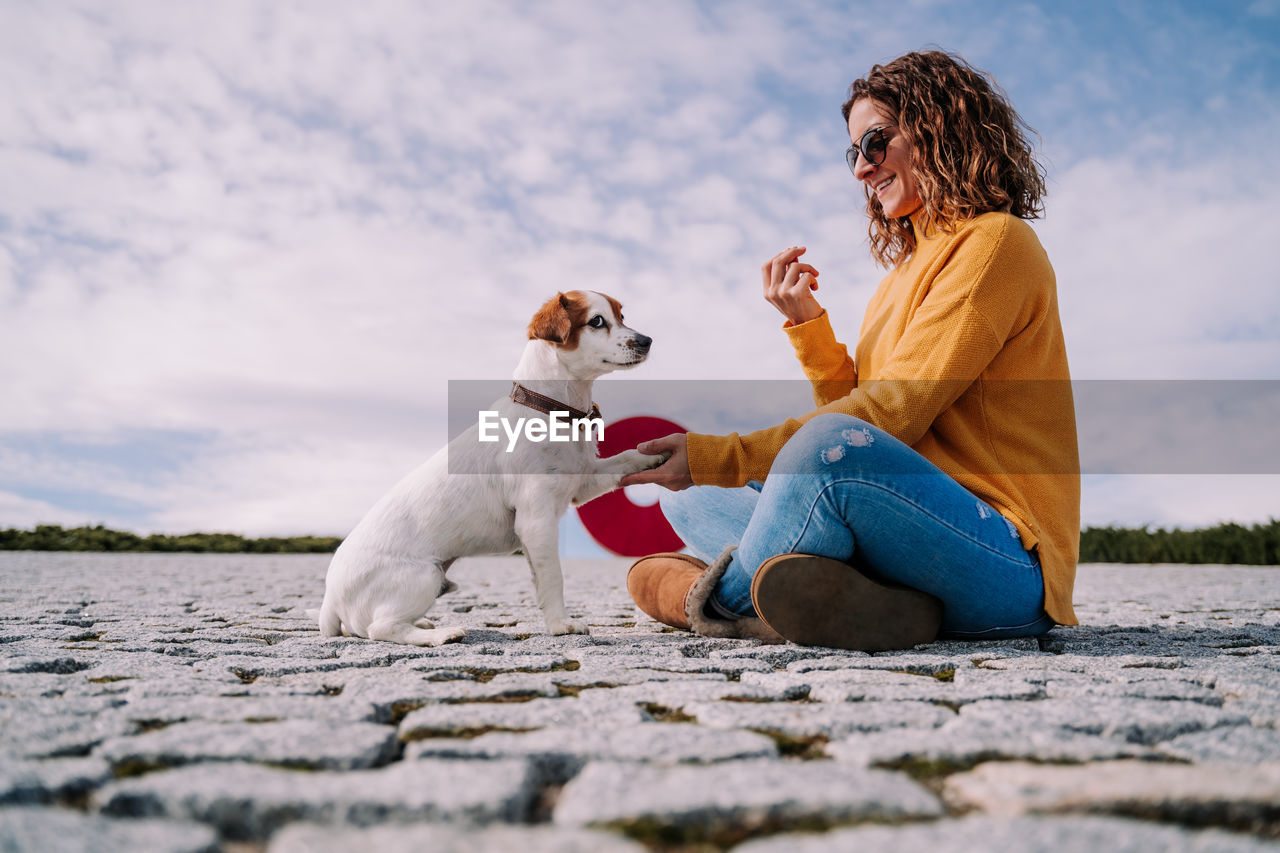 Man with dog sitting outdoors