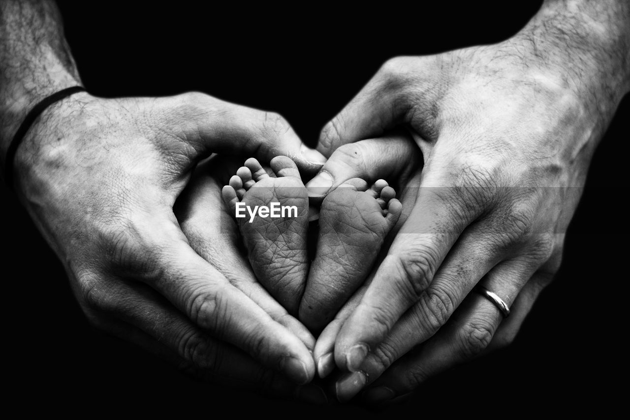 Close-up of parents hands holding baby