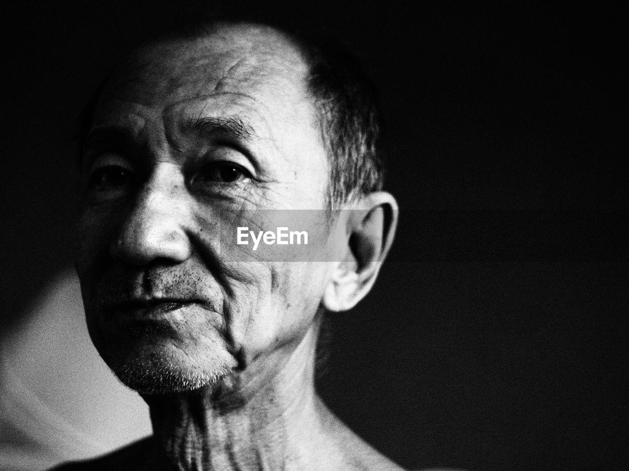 Close-up portrait of senior man in darkroom