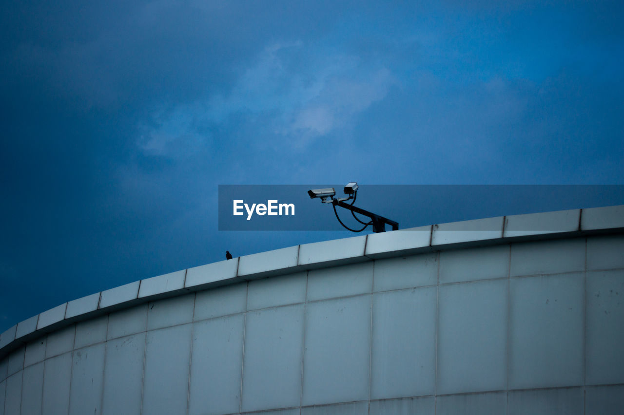 Low angle view of man climbing on building against sky