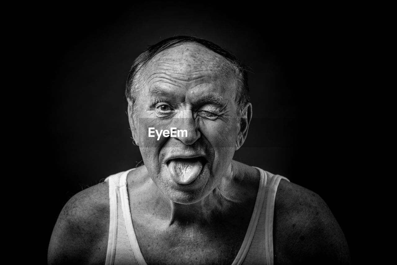 senior adult, studio shot, black background, portrait, senior men, indoors, wrinkled, front view, one person, adult, headshot, looking at camera, lifestyles, emotion, close-up, tank top, males, cut out, mouth open, human face, aggression
