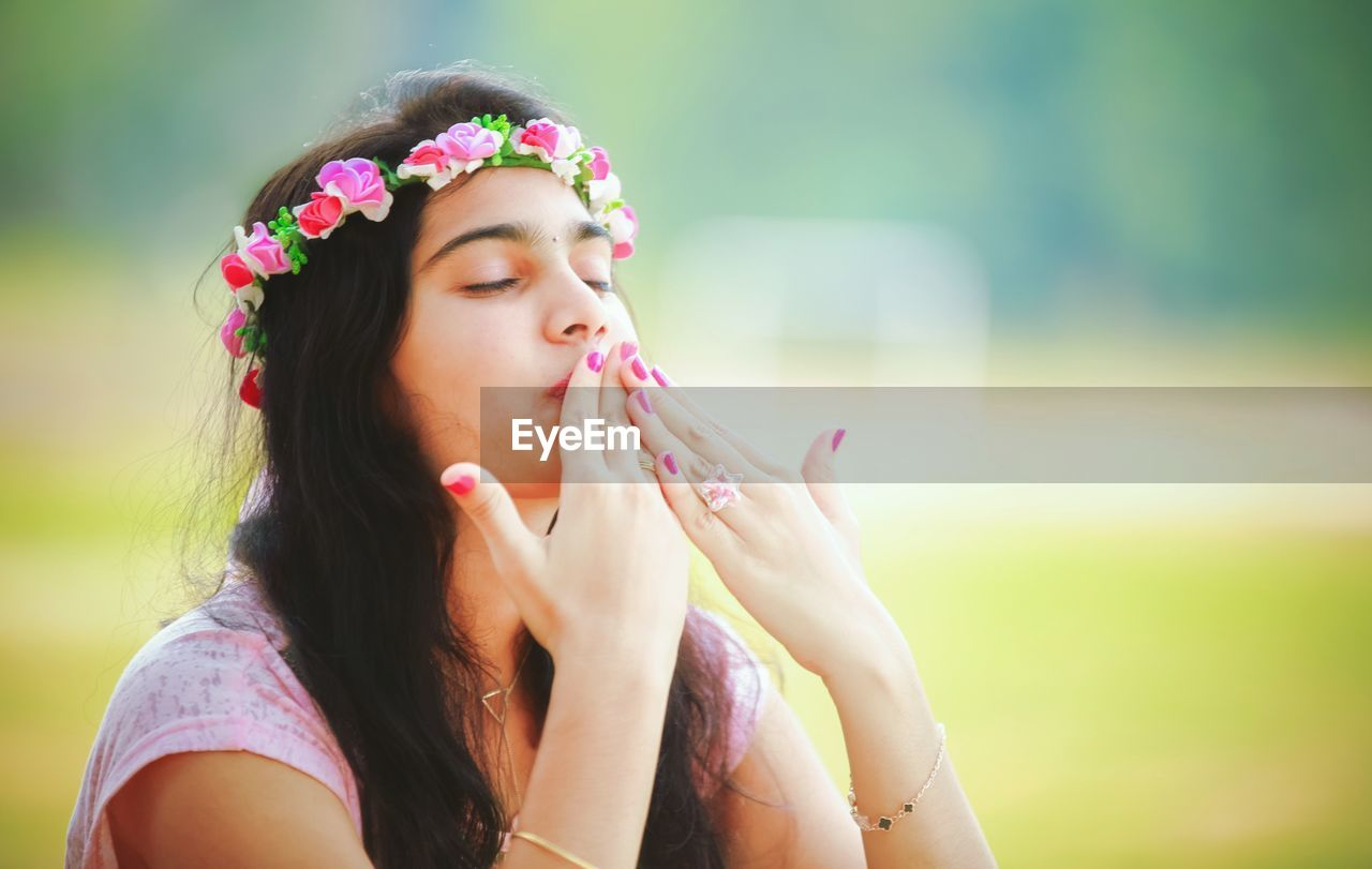 Young Woman With Eyes Closed Blowing Kiss In Park