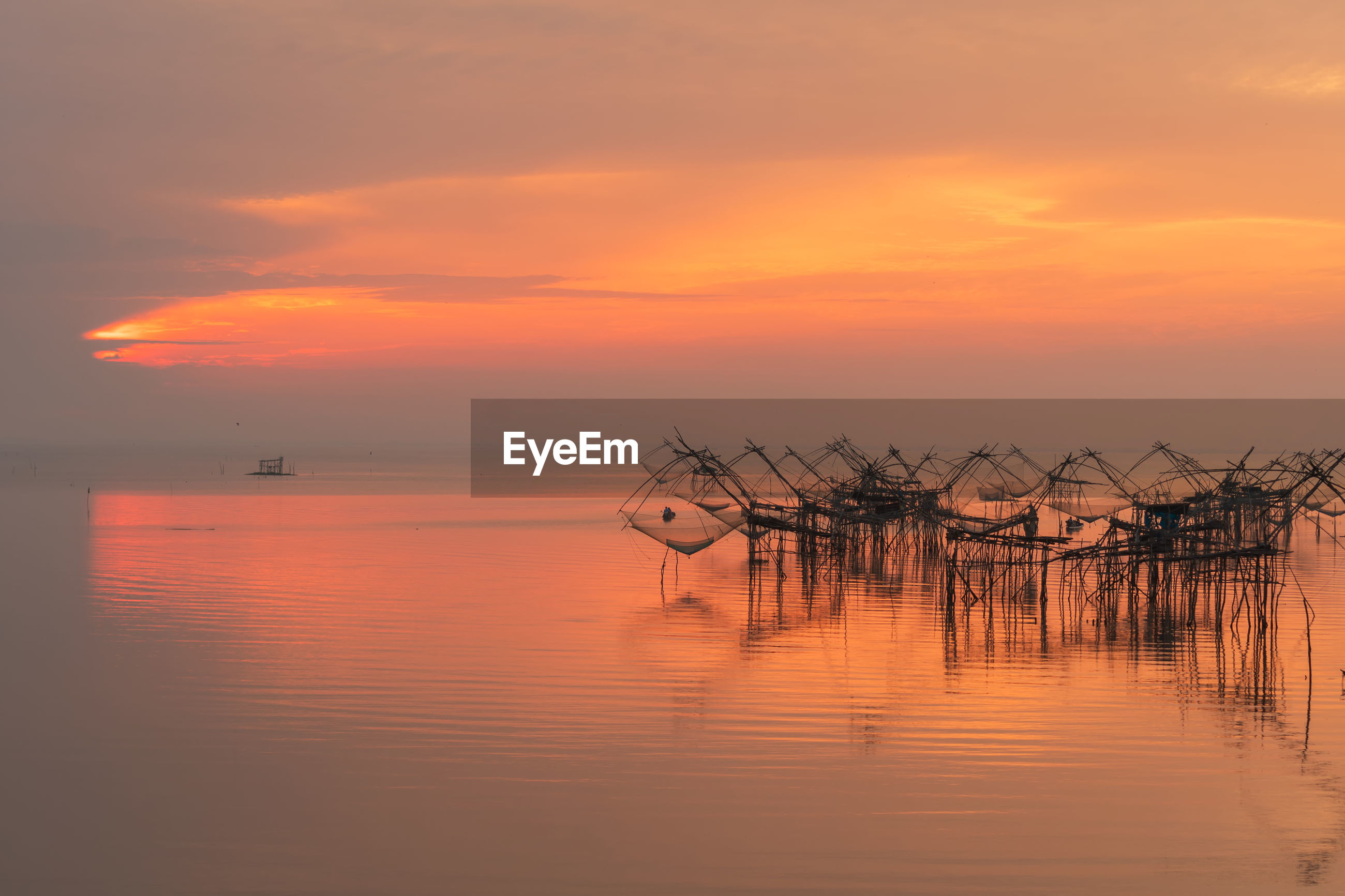 Scenic view of sea with fishing nets against orange sky