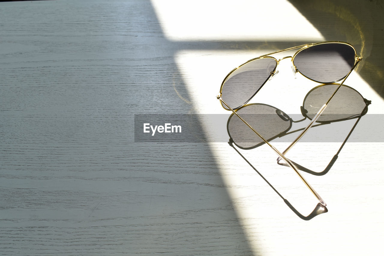 glasses, sunlight, sunglasses, shadow, no people, table, eyeglasses, fashion, personal accessory, reflection, still life, nature, day, single object, high angle view, transparent, indoors, close-up, glass - material, eyewear