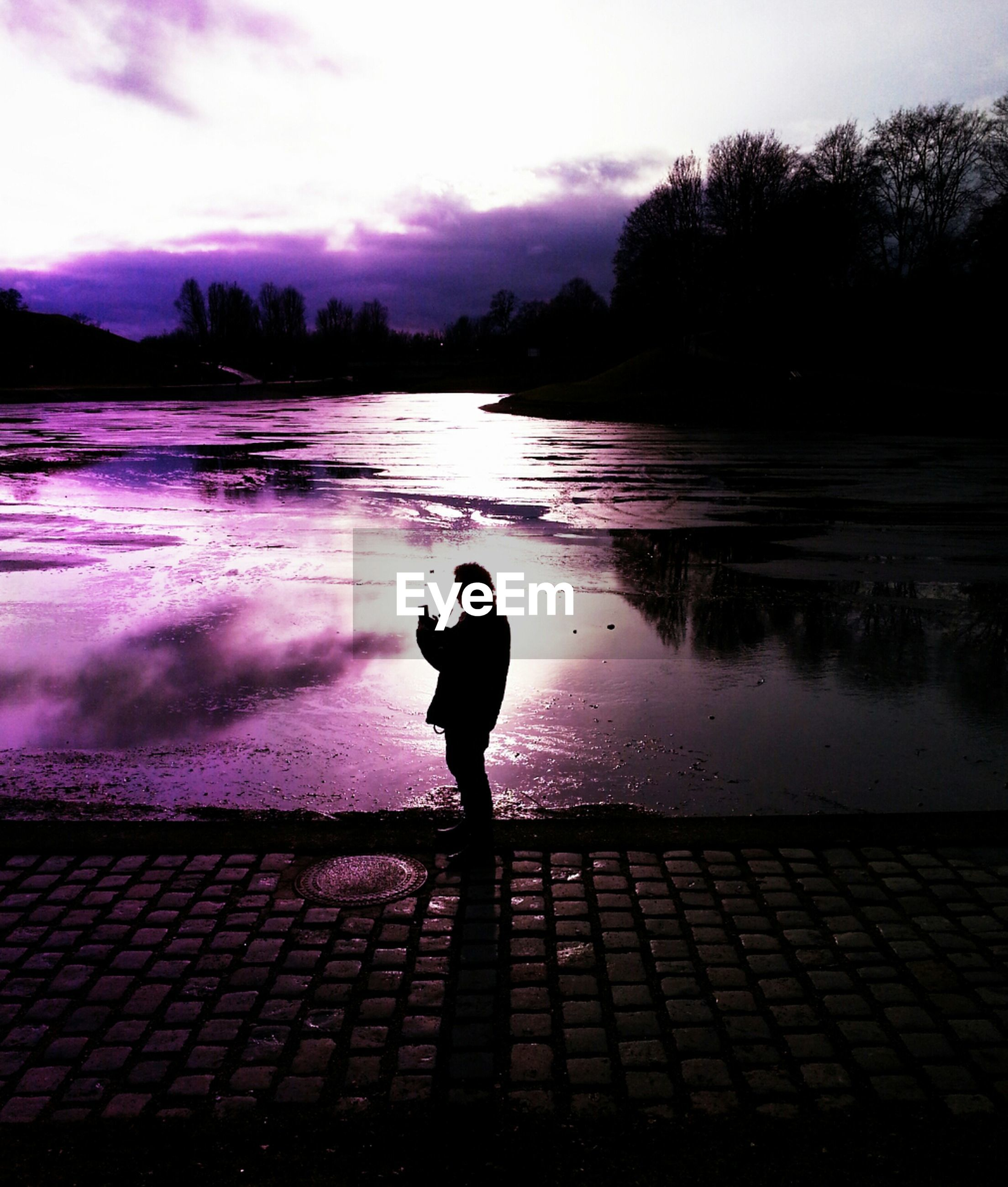 Side view of a silhouette man by calm lake