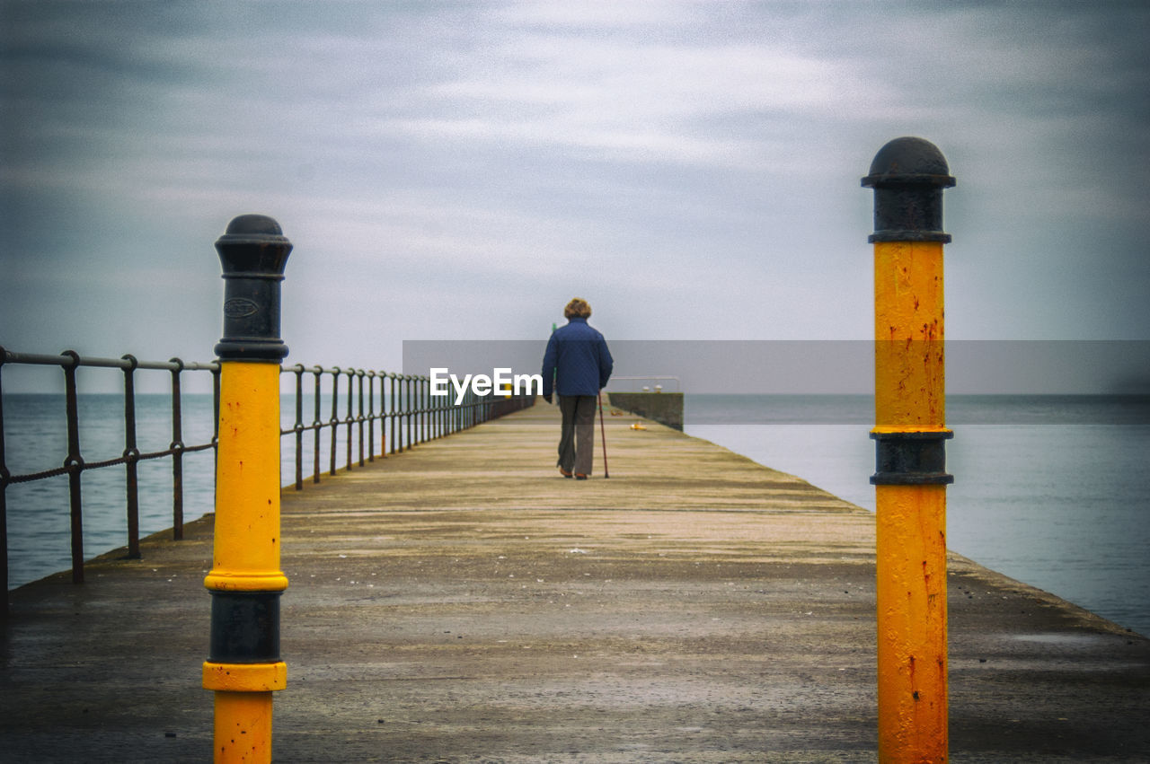 rear view, full length, water, sky, one person, real people, pier, lifestyles, leisure activity, sea, yellow, beauty in nature, men, standing, day, cloud - sky, scenics - nature, casual clothing, outdoors, post, architectural column