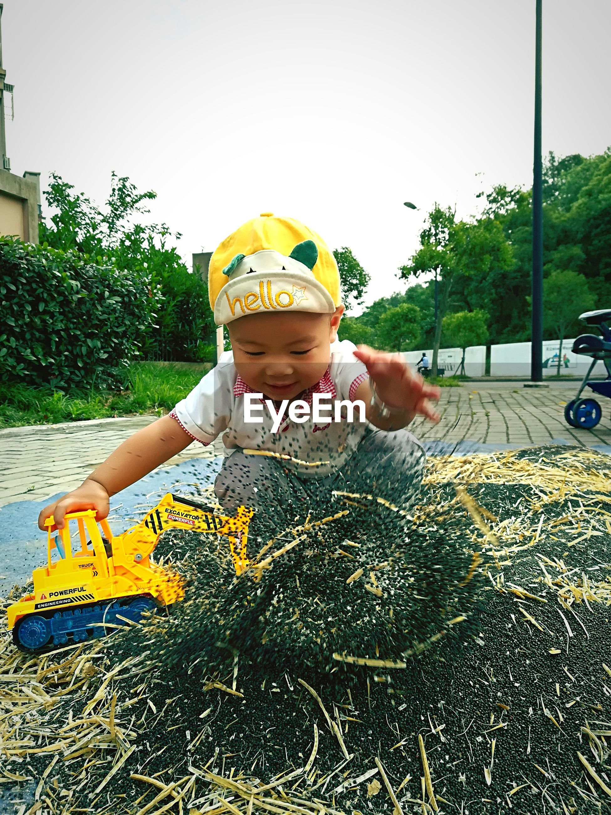 Baby boy splashing dirt at playground