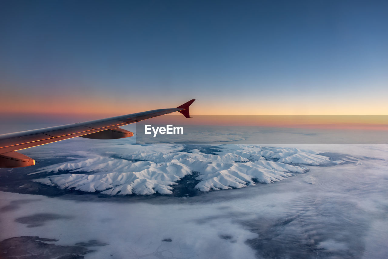 sky, sunset, scenics - nature, beauty in nature, winter, cold temperature, airplane, air vehicle, snow, tranquil scene, transportation, mode of transportation, nature, aircraft wing, no people, travel, tranquility, orange color, flying, snowcapped mountain