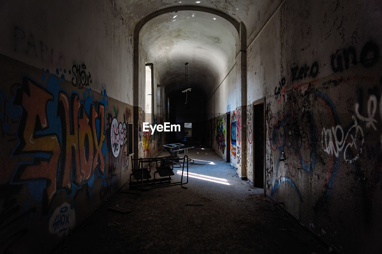 graffiti, architecture, wall - building feature, indoors, abandoned, building, built structure, creativity, art and craft, direction, the way forward, illuminated, no people, corridor, tunnel, arcade, multi colored, text, paint, messy, ceiling, deterioration, ruined