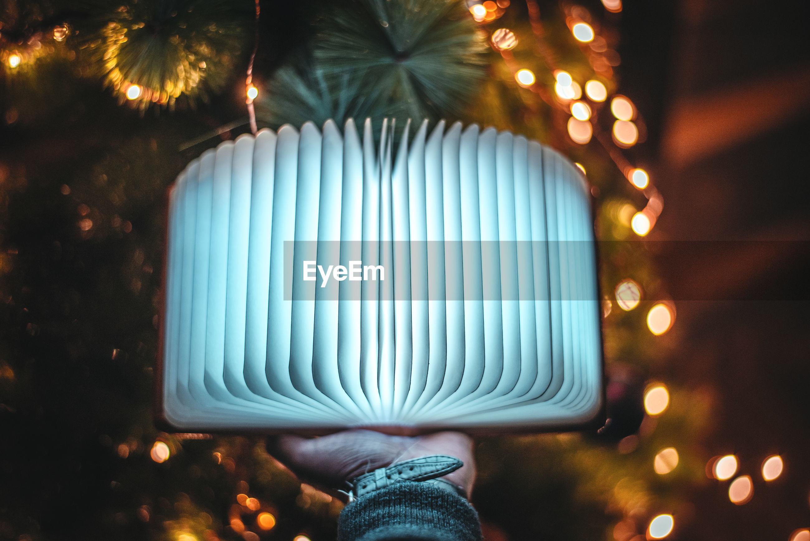 Close-up of hand holding illuminated lighting equipment at night