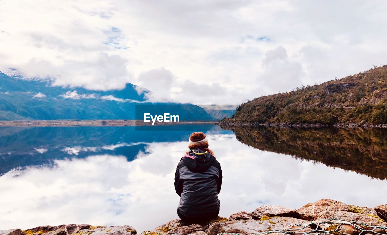 Rear view of woman sitting by lake against cloudy sky during winter