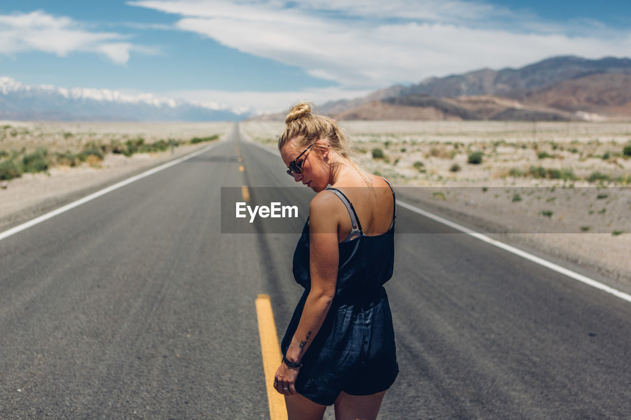 Rear View Of Young Woman Walking On Road Against Sky