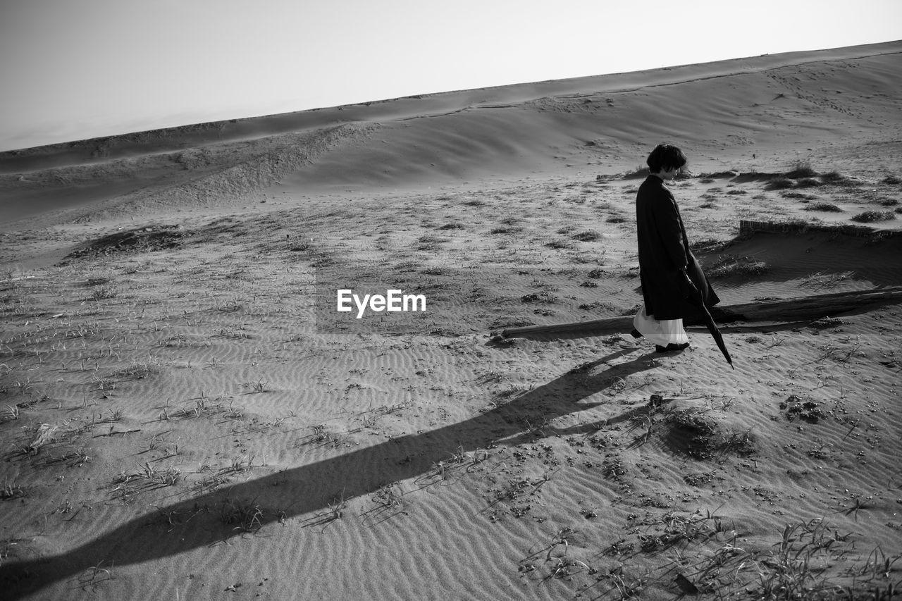 Tilt image of woman walking in desert against clear sky