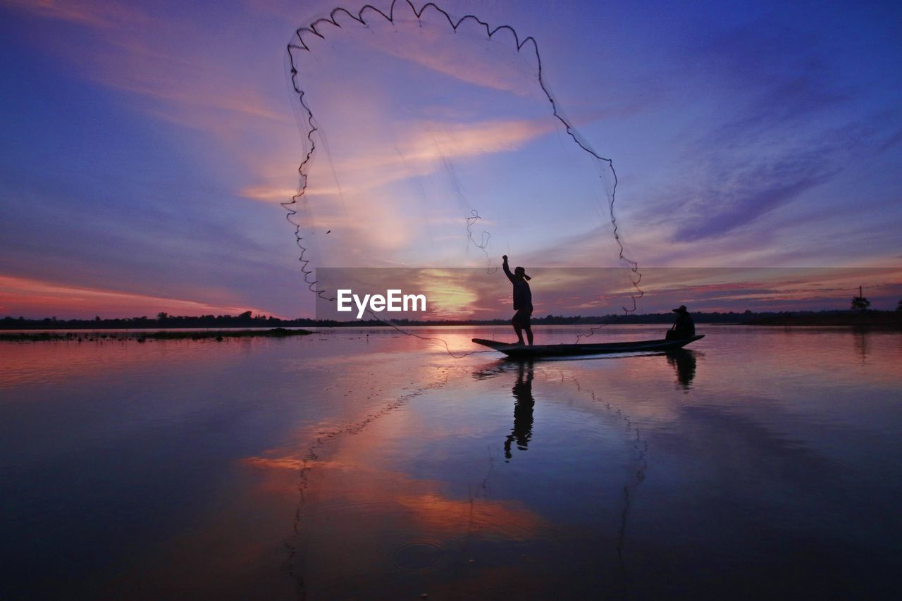 Silhouette fisherman casting fishing net in lake against dramatic sky during sunset