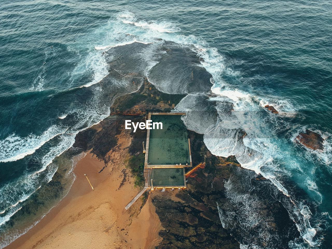 Aerial view of waves breaking on rocks