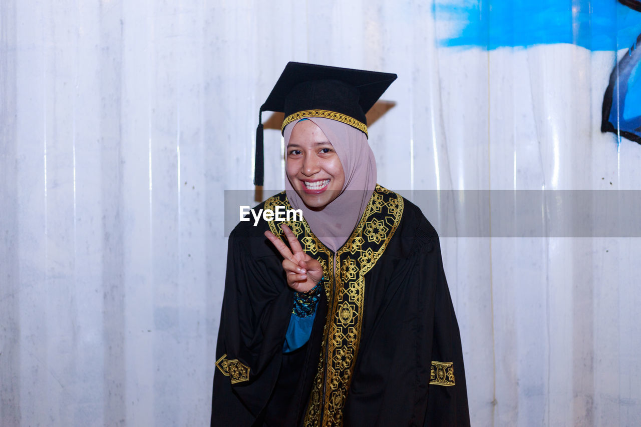 Portrait Of Smiling Young Woman Wearing Mortar Board While Standing Against Wall