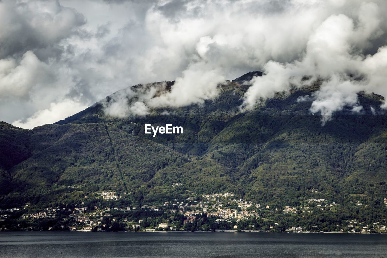 Lake maggiore in front of mountains against cloudy sky