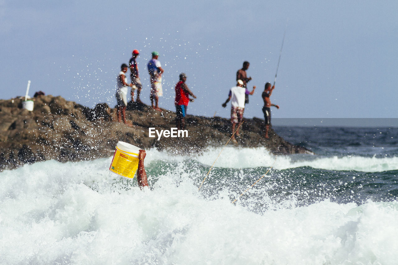 Cropped Hand Holding Bucket In Surf With Men Fishing In Background