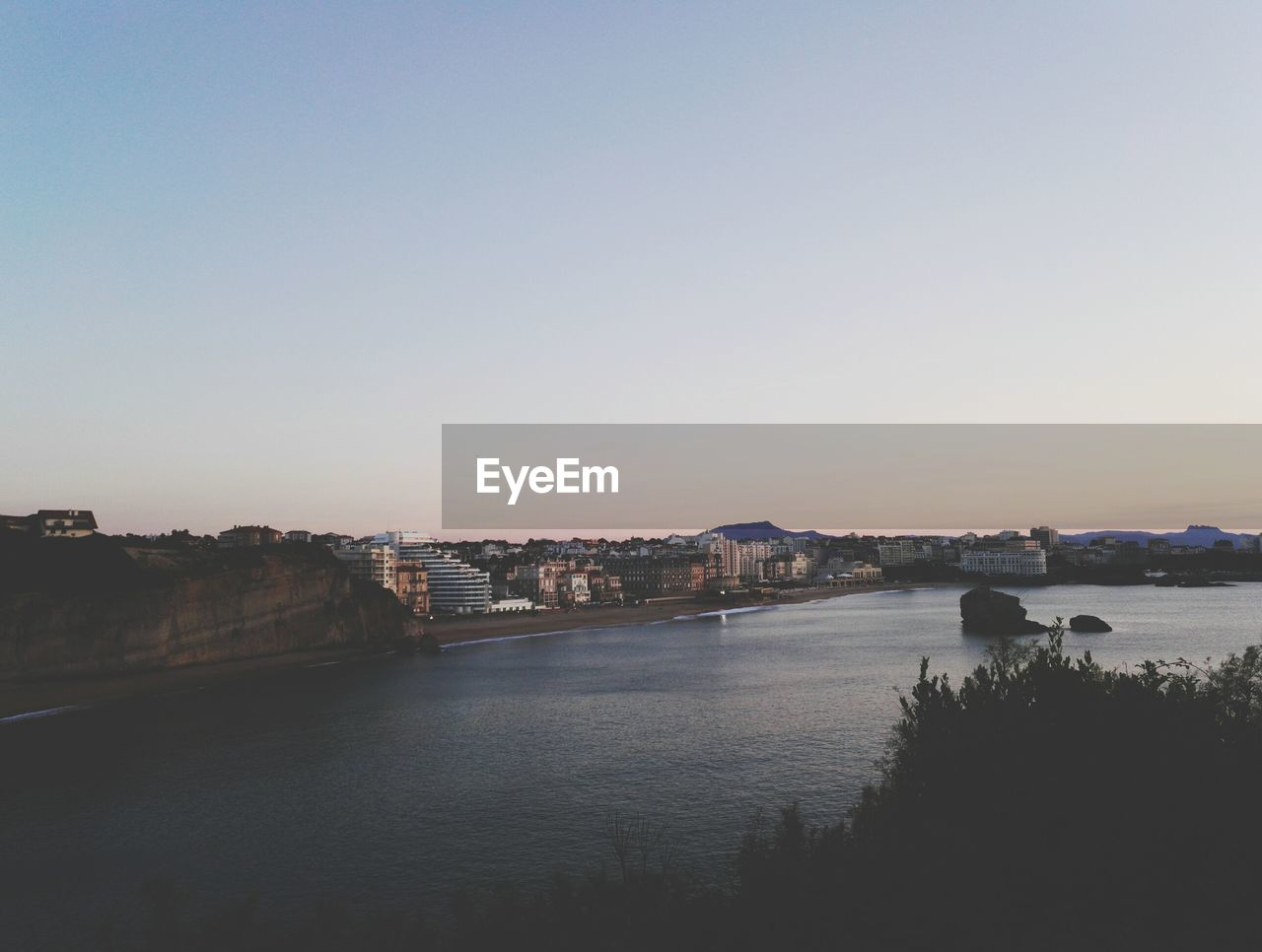 architecture, built structure, water, river, city, copy space, cityscape, building exterior, connection, clear sky, outdoors, no people, travel destinations, bridge - man made structure, sunset, nature, chain bridge, sky, day