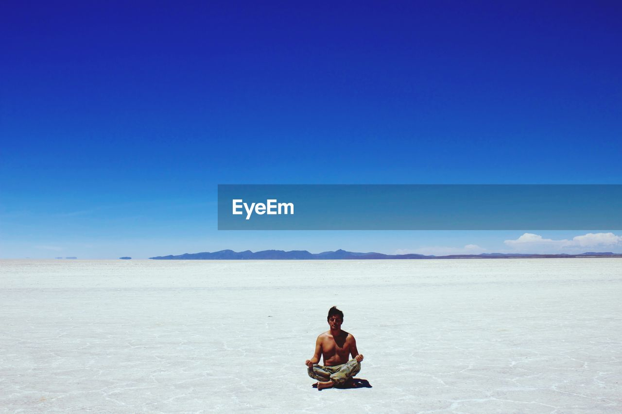 Full Length Of Shirtless Man Meditating On Salt Flat Against Blue Sky During Sunny Day