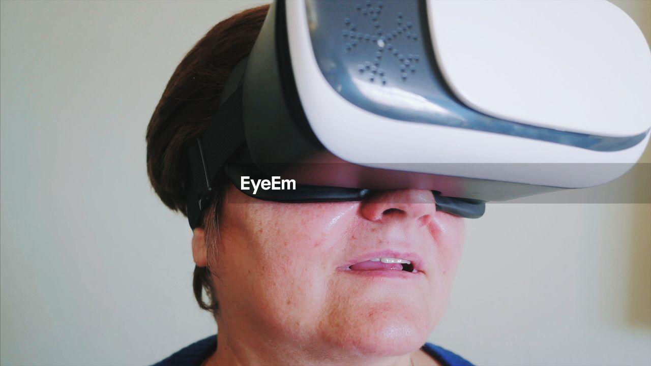Woman wearing virtual reality simulator against wall