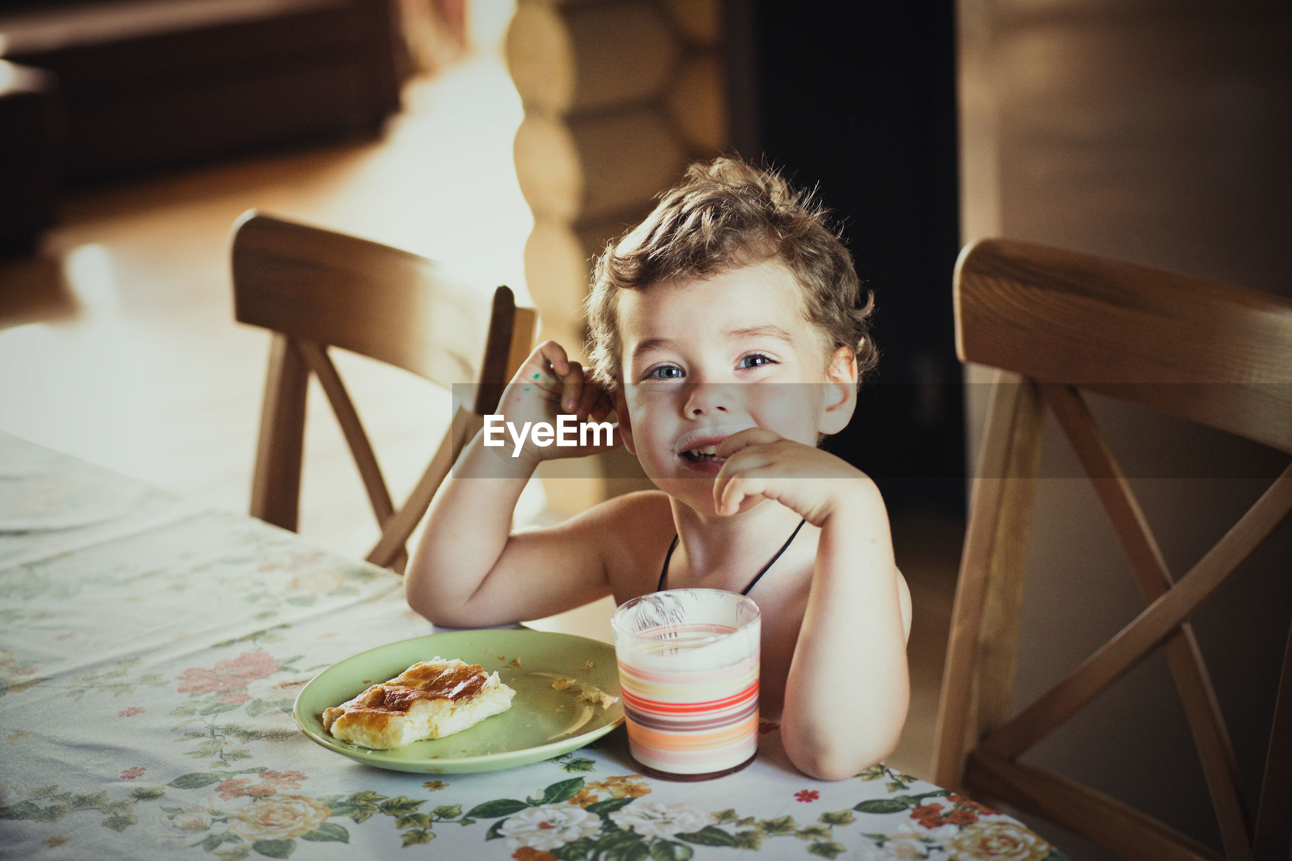 Portrait of boy having breakfast at table in home