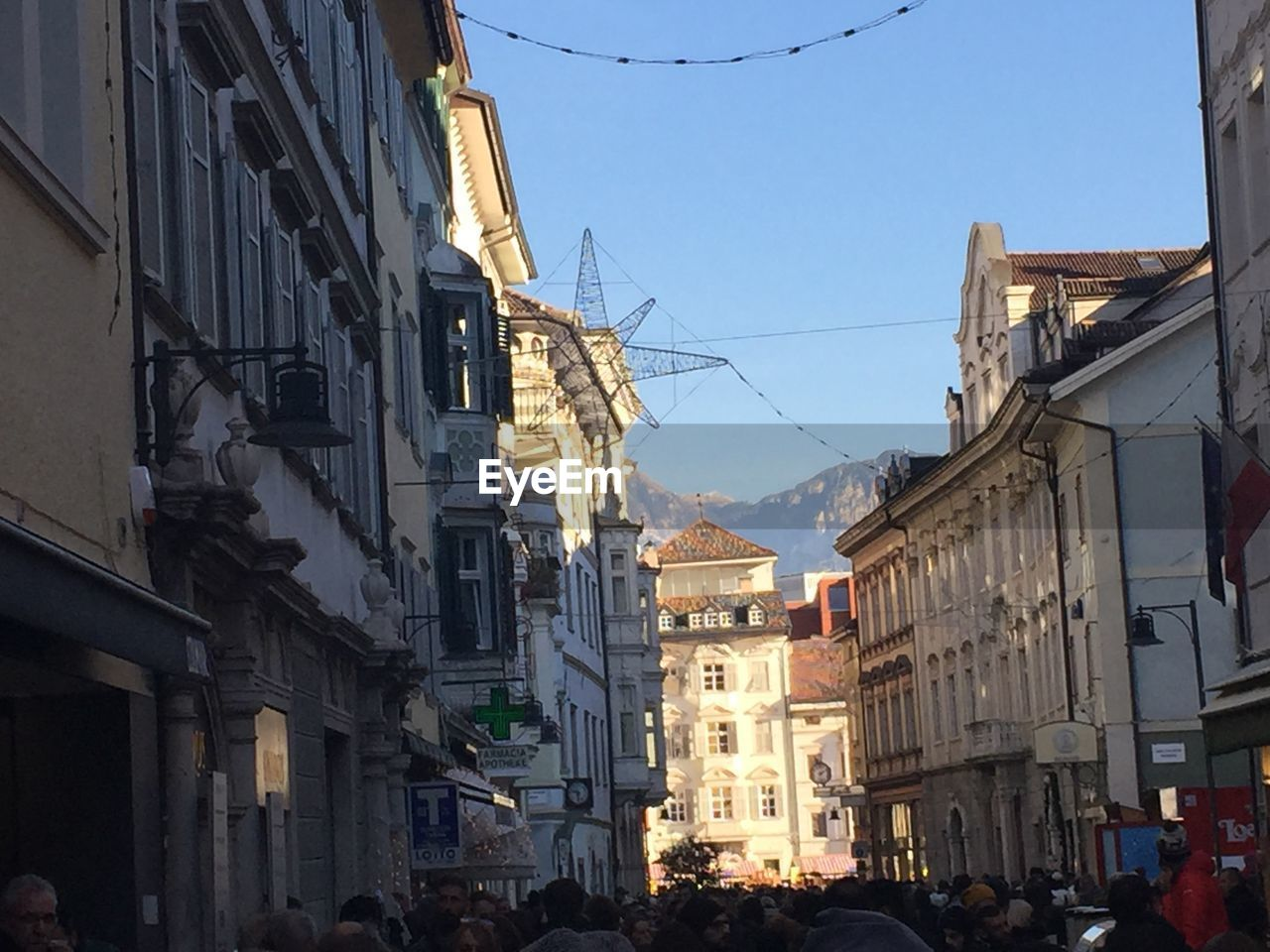 building exterior, architecture, built structure, city, building, sky, residential district, nature, day, clear sky, street, outdoors, incidental people, cable, real people, mountain, group of people, sunlight, town, motor vehicle