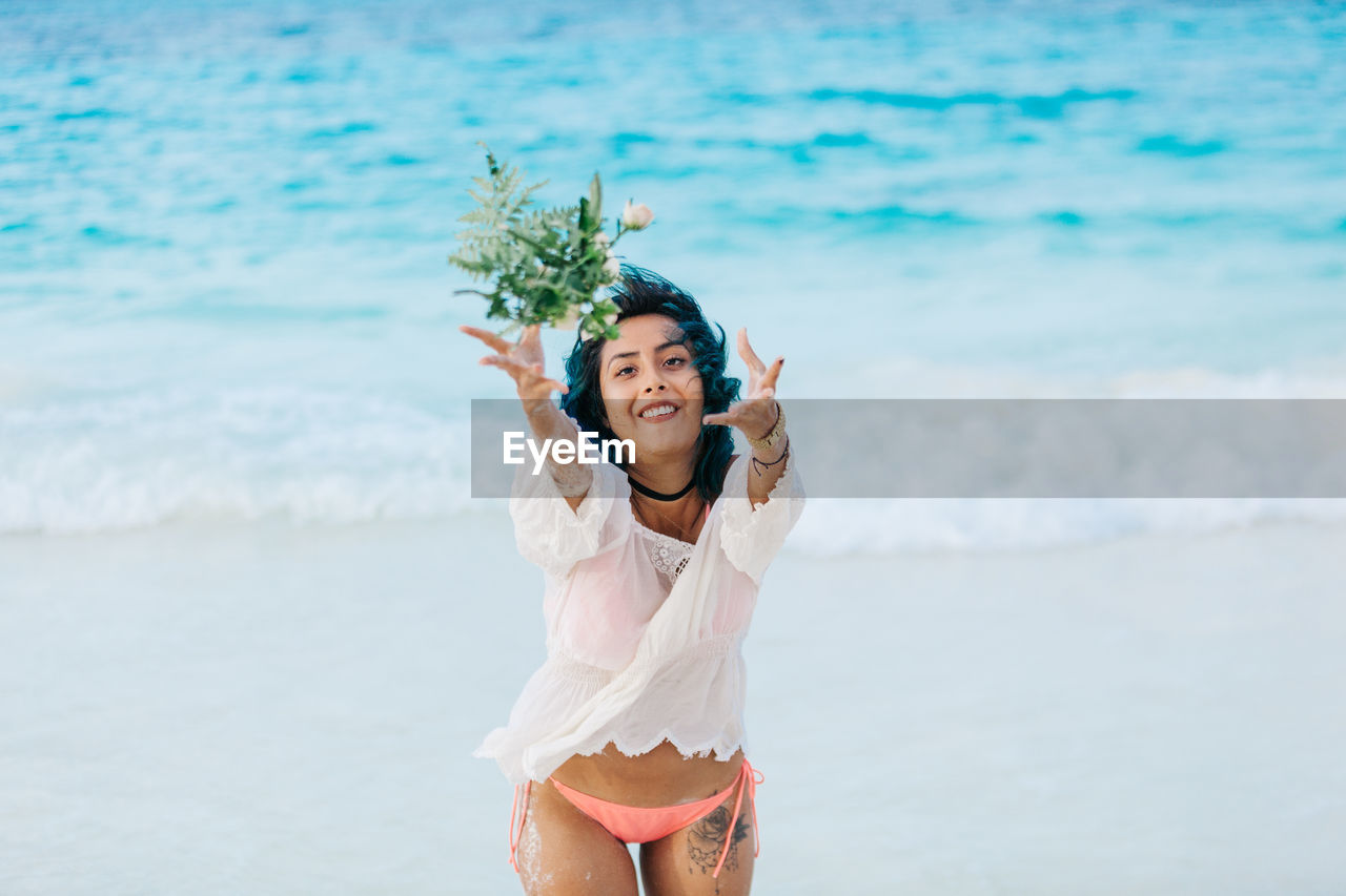 sea, water, three quarter length, real people, one person, beach, leisure activity, lifestyles, land, nature, front view, young adult, women, standing, day, adult, happiness, emotion, human arm, arms raised, bouquet, outdoors, flower arrangement