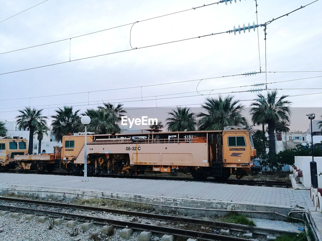 railroad track, transportation, cable, mode of transport, rail transportation, power line, train - vehicle, sky, day, public transportation, outdoors, electricity pylon, land vehicle, no people, tree, nature