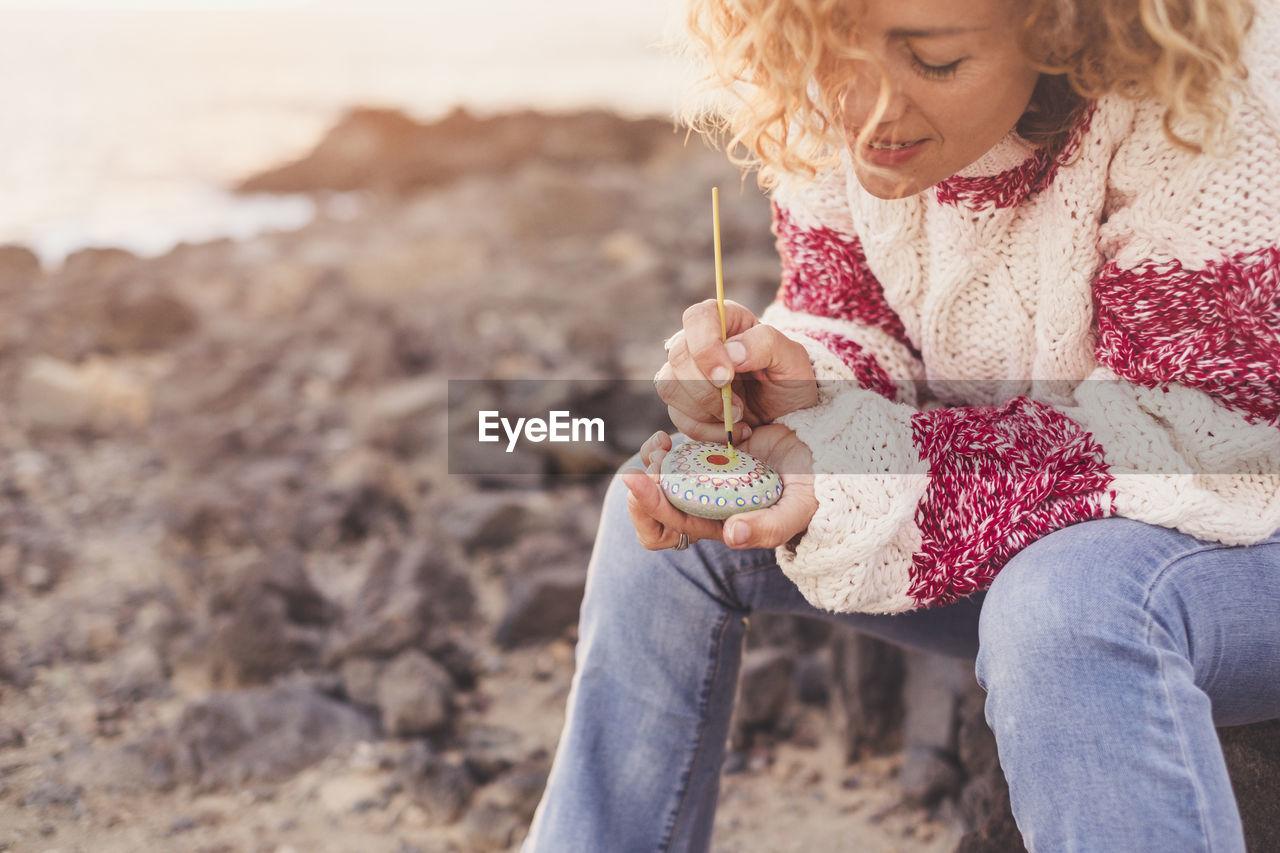 Mature Woman Painting Pebble At Shore