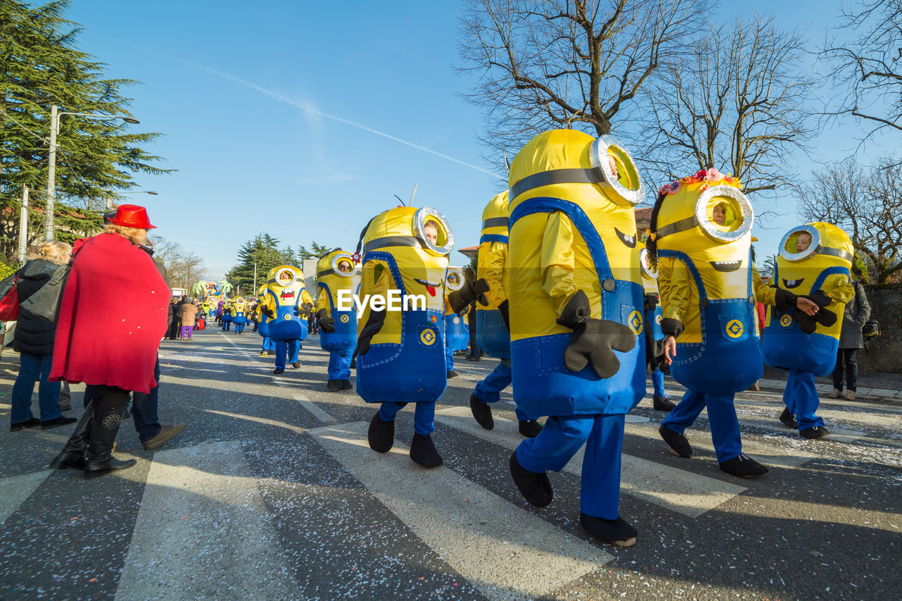 large group of people, day, real people, yellow, men, tree, outdoors, road, togetherness, lifestyles, full length, women, teamwork, sky, people