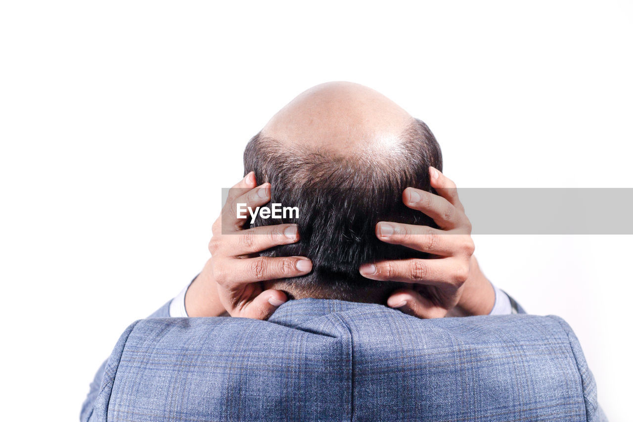 Rear view of balding businessman touching head against white background