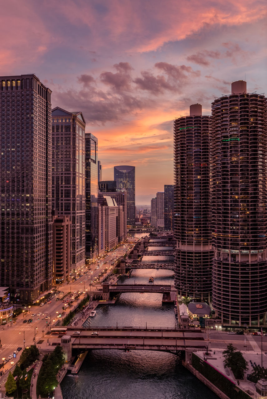 Aerial View Of Chicago River Amidst Modern Buildings In City At Sunset