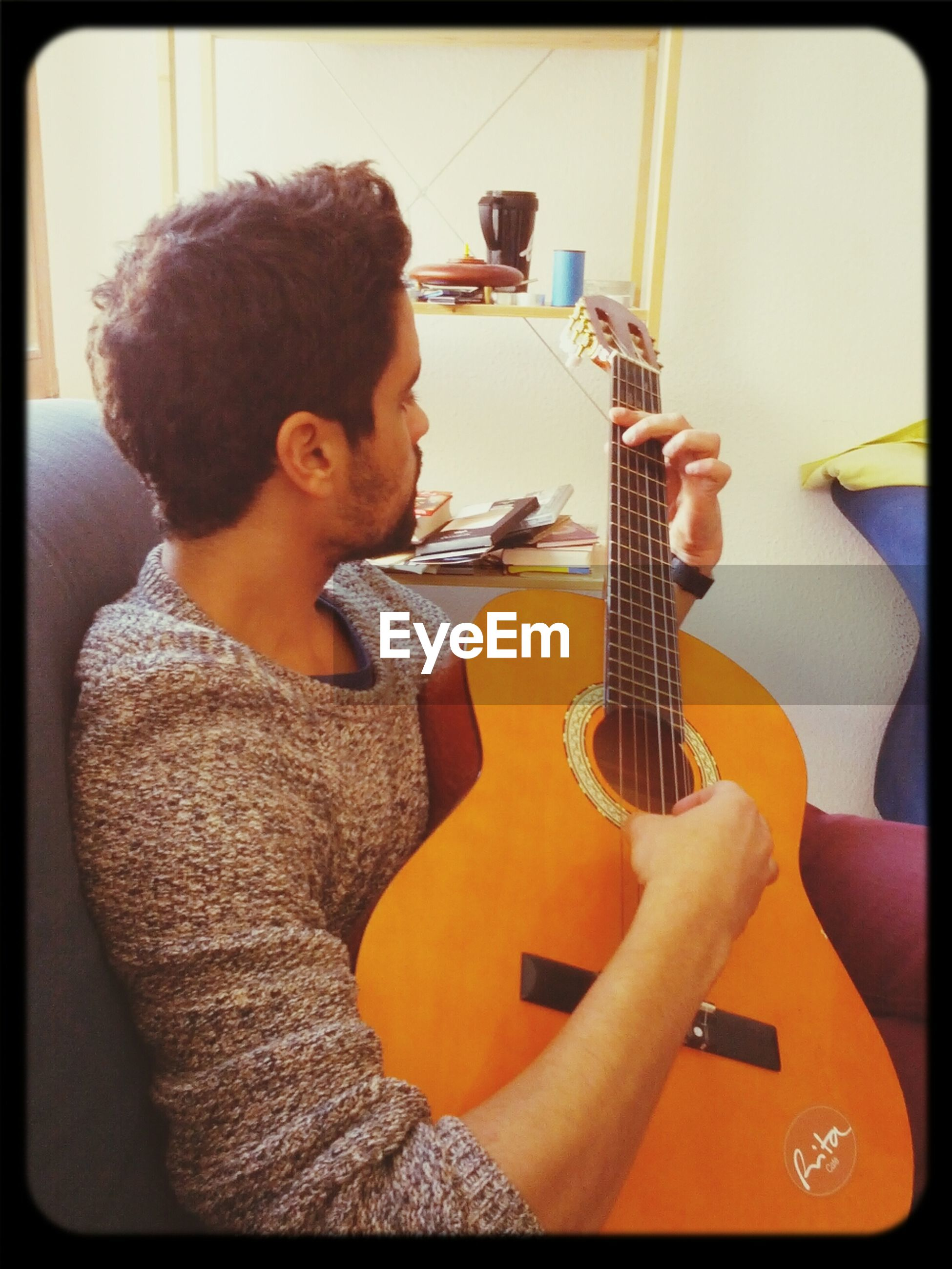 indoors, transfer print, musical instrument, guitar, music, holding, lifestyles, arts culture and entertainment, leisure activity, casual clothing, playing, auto post production filter, person, technology, wireless technology, home interior, front view, childhood