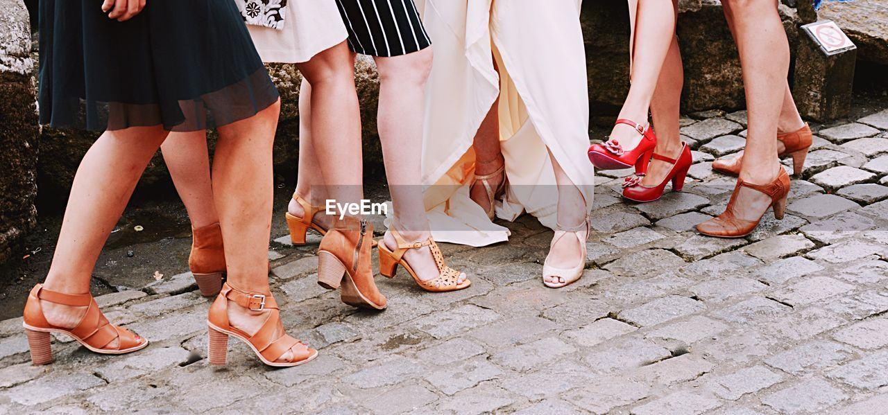 low section, group of people, body part, human leg, human body part, women, real people, shoe, standing, fashion, footpath, lifestyles, adult, day, cobblestone, togetherness, people, street, outdoors, leisure activity, paving stone, human foot, human limb