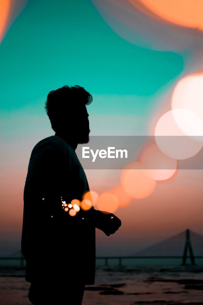 Silhouette Man Standing Against Defocused Light During Sunset