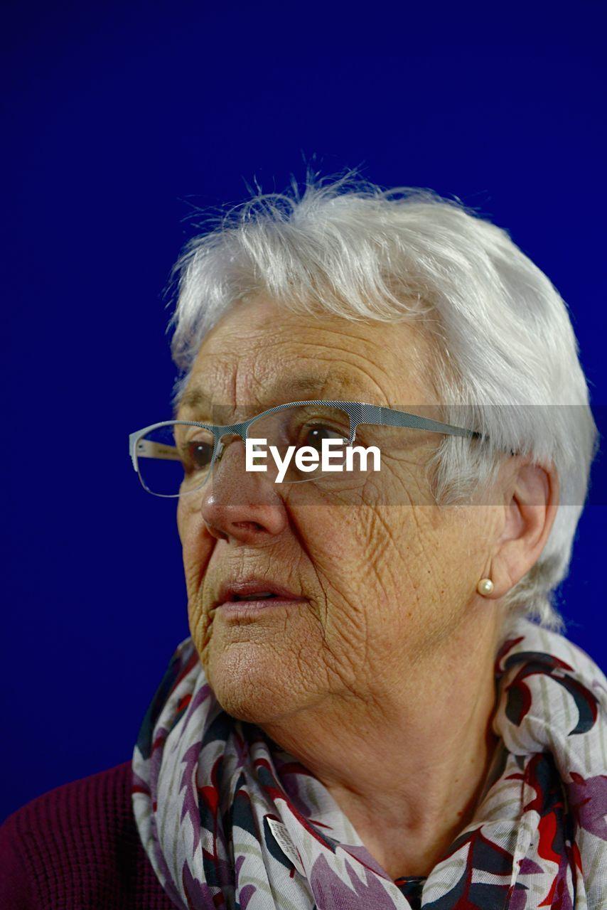 Close-Up Of Thoughtful Senior Woman Wearing Eyeglasses Against Blue Background
